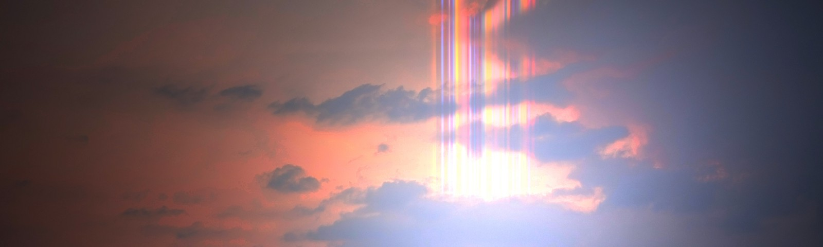 Beautiful rainbow flare in the sunset sky with bright light.