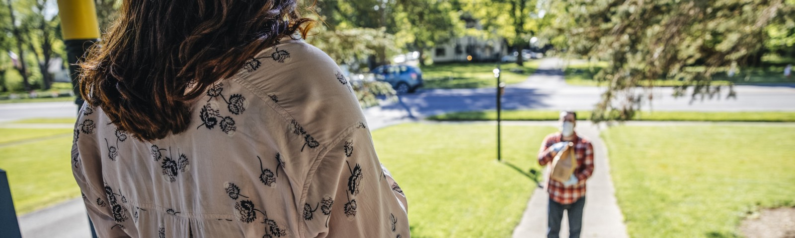 A person on their front porch, looking out at their neighborhood; on their front walk stands a person delivering a bag.