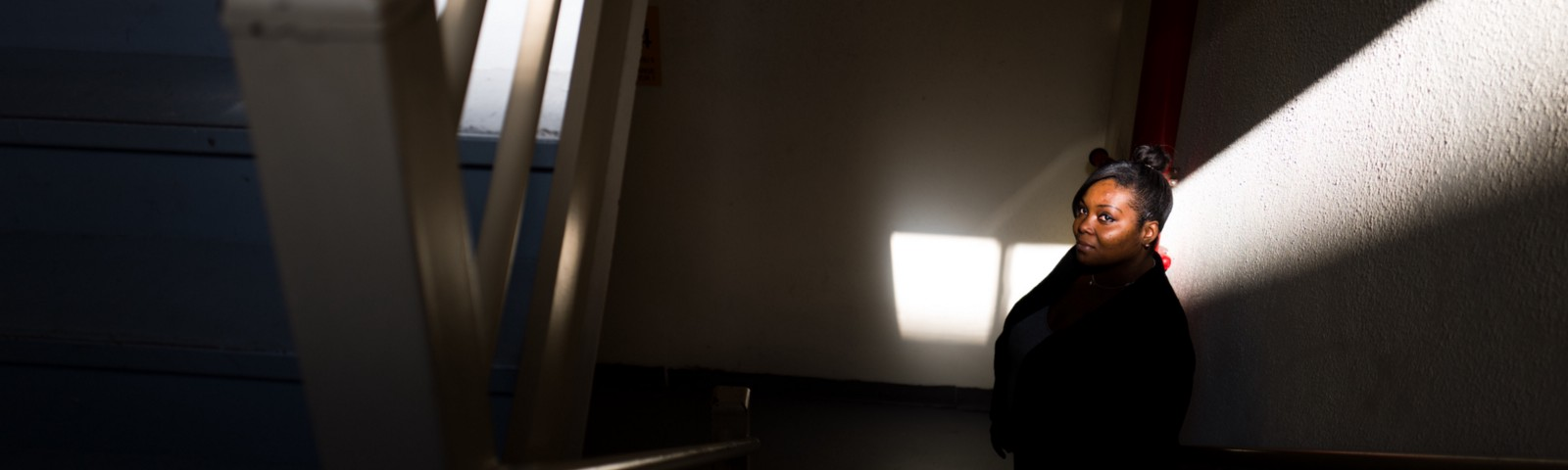Arlene in a dark stairwell, her face highlighted by a shaft of light