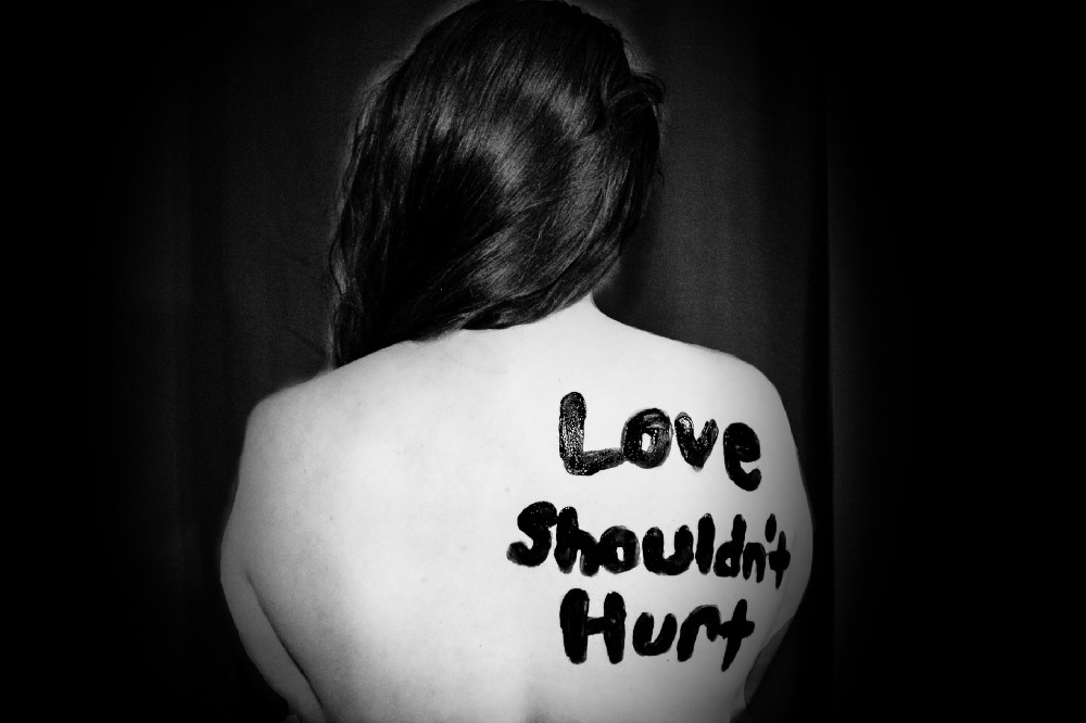 "A photograph of a woman with her back turned, who has, ""Love Shouldn't hurt"" written on her back. It is meant to depict how financial abuse hurts even thought it's not physical abuse."