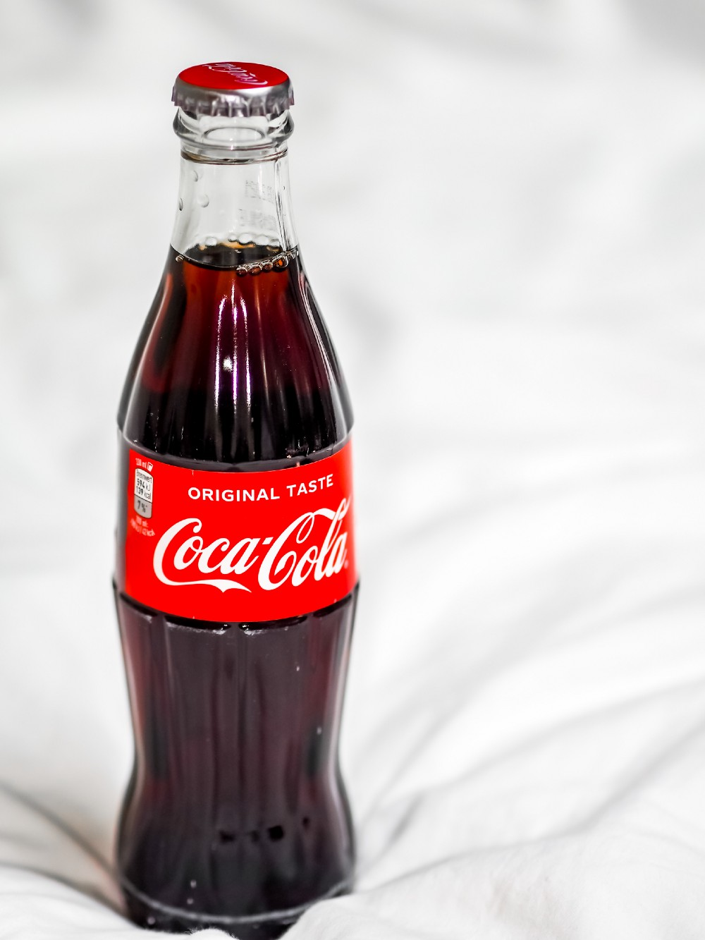 the iconic coca-cola glass bottle on a mattress, close-up.
