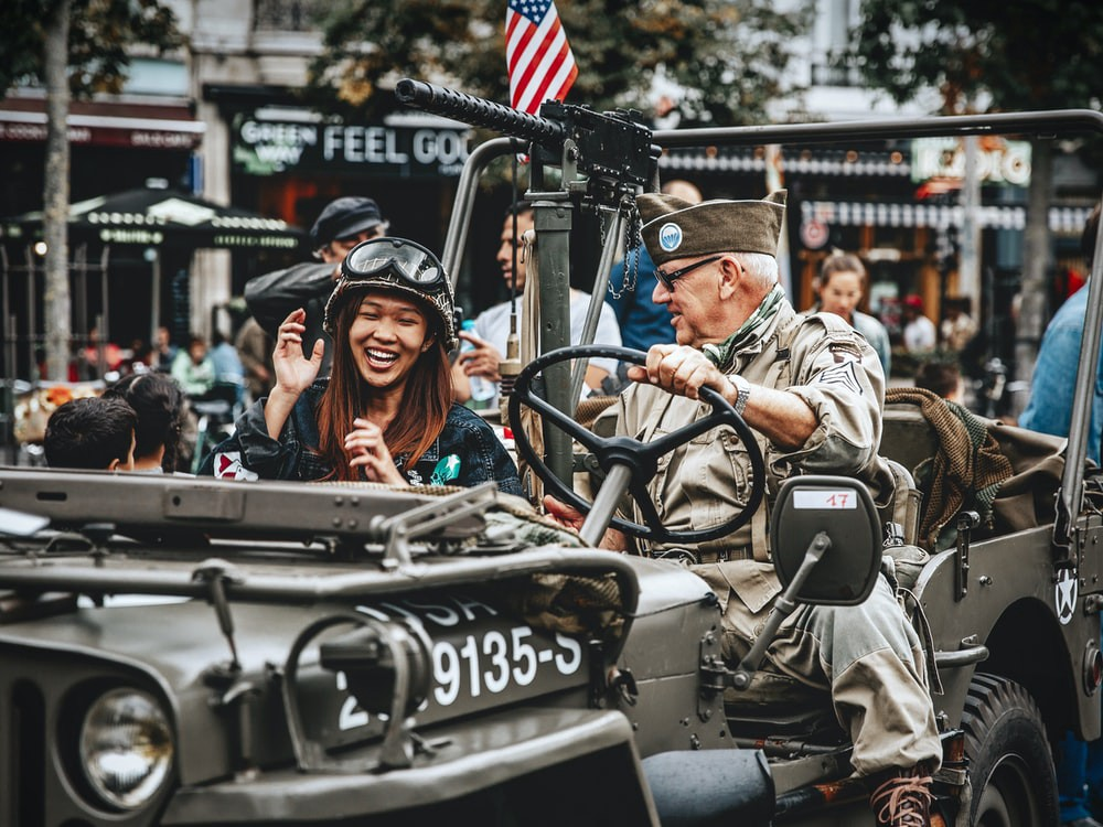 An old soldier conducing a truck in a parade with a young woman laughing in the passenger seat.