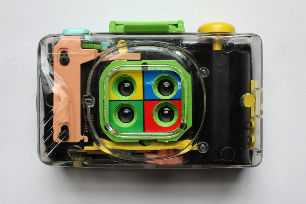 Clear plastic camera with four lenses, each surrounded by a different color.