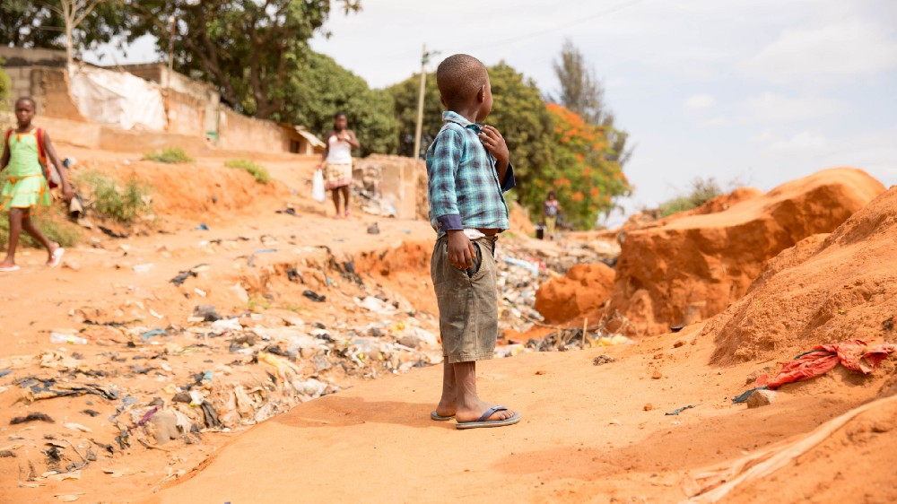 A young boy stands in the middle of a dirt road littered with garbage.