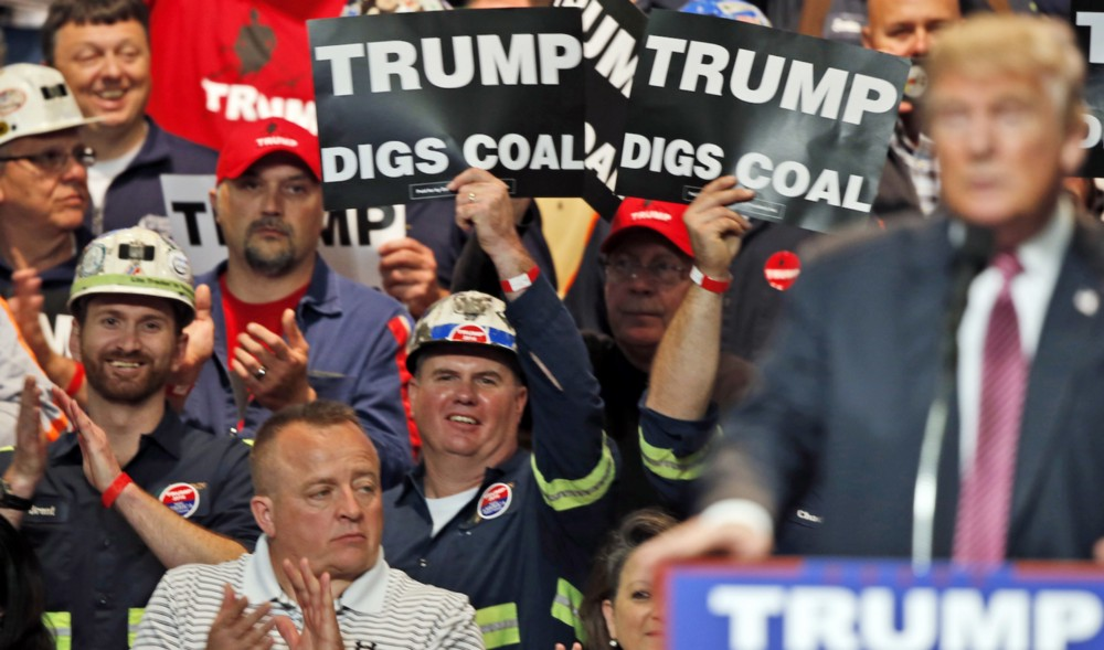 Coal miners wave signs as candidate Donald Trump speaks during a May 5, 2016 rally in West Virginia. CREDIT: AP Photo/Steve Helber
