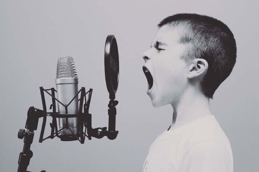 Black and white photo of boy shouting into a microphone