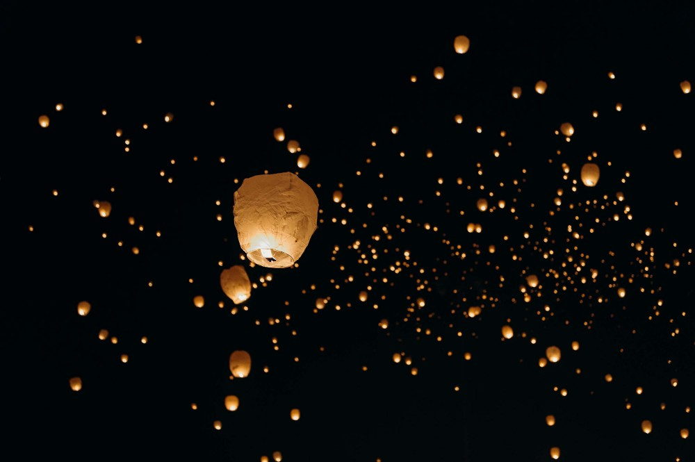Hundreds of paper lanterns sailing away on a dark night
