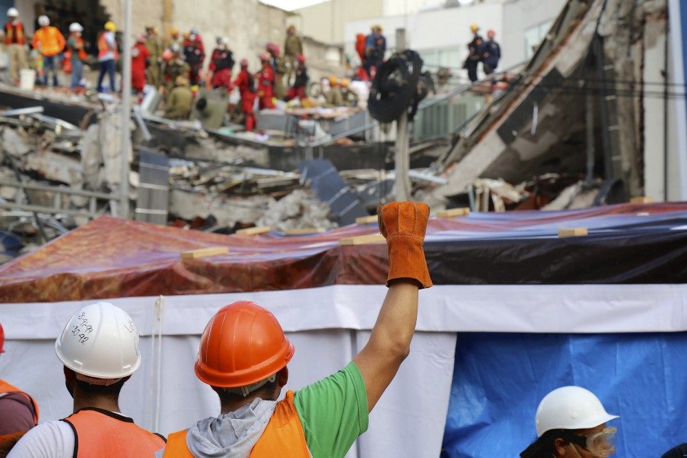 Workers at the site would periodically raise their fists to call for silence so rescuers could listen for sounds of survivors in the rubble.