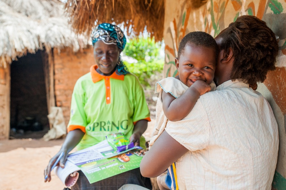 Salima Muyodi, a community-based village health team member, explains how to use micronutrient powders to a mother in Namutumba. / SPRING
