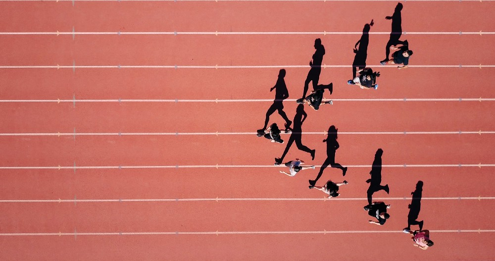 Track runners pictured from above, running in separate tracks.