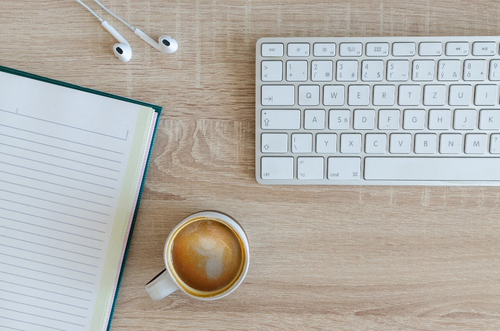 Flatlay of a desk. Shows keyboard, cup of brown beverage, white earphones and a blank notebook