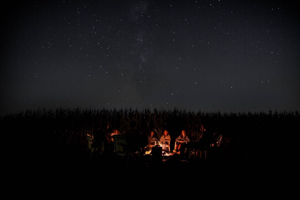 A group of people telling stories around a campfire.