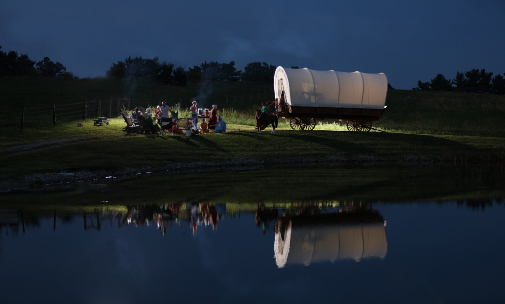 covered wagon beside a campfire, reflected in a lake