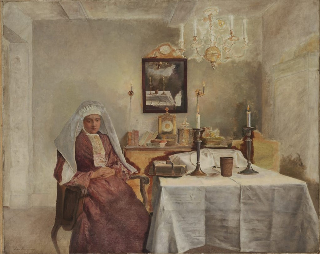 Woman wearing a long red dress & white hair cover sitting at table with a kiddush cup and Torah in a warmly lit white room.