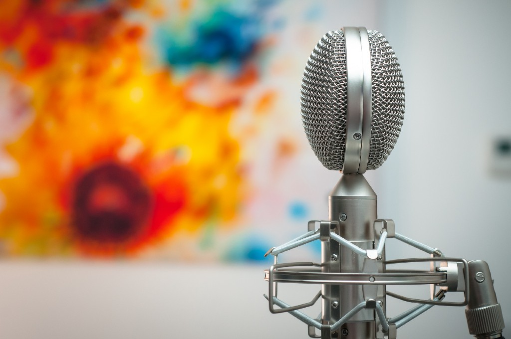 A silver microphone with a painting in the background