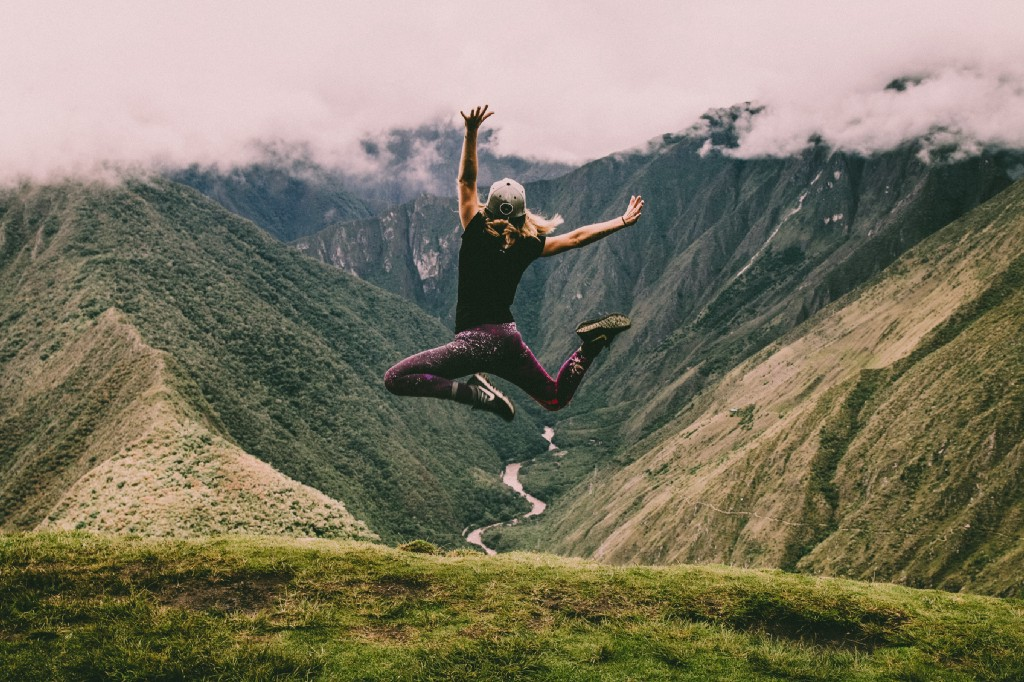 person leaping joyfully, green mountains in background