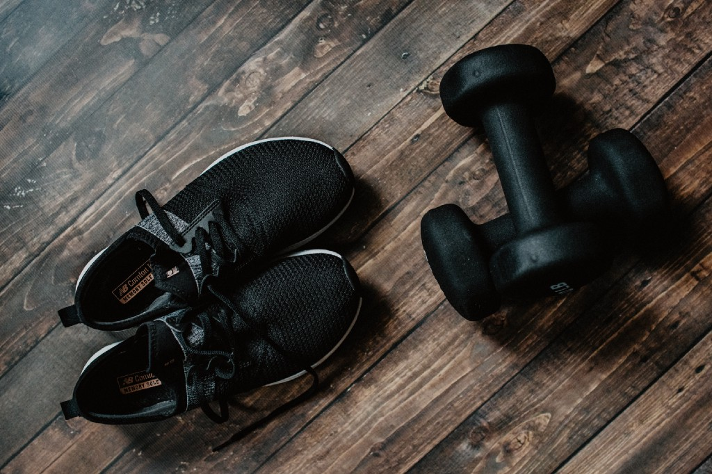 Photo of a pair of gym shoes and dumbbells.