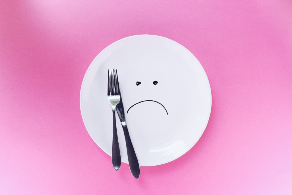a metal spoon and fork placed on a plate with a frown face drawn on it