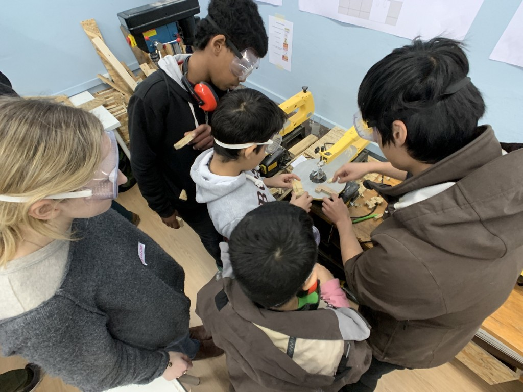 Children in safety goggles working with tools in a classroom