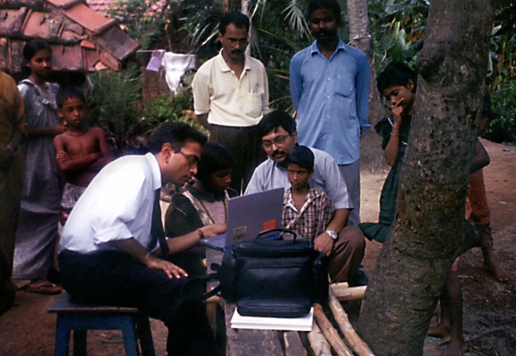 Man in business attire sits showing a group of families information on a laptop