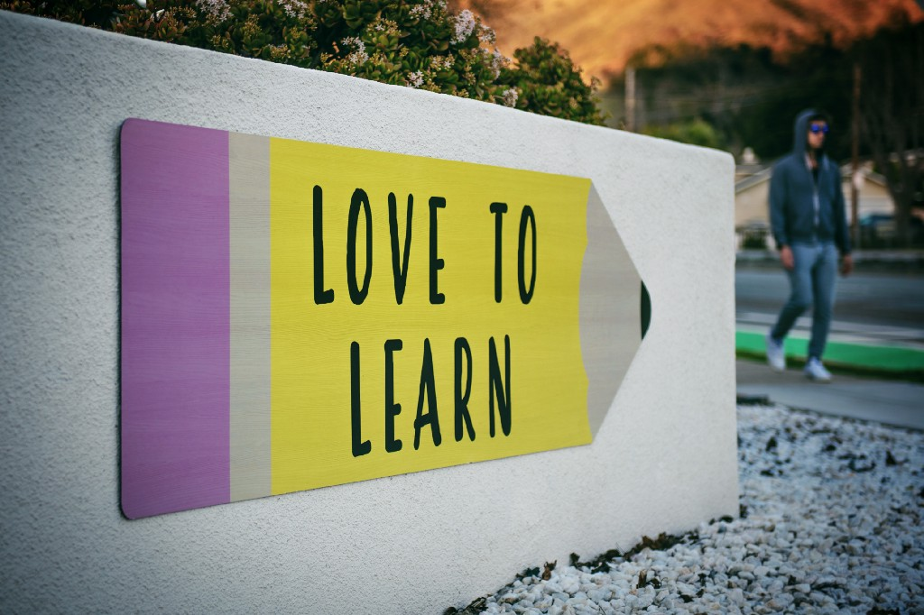 """An arrow-shaped sign with the text """"love to learn"""""""