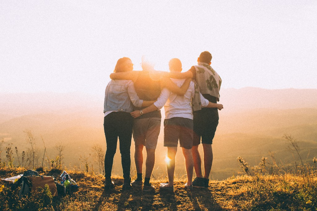 four people with their arms over each other's shoulders, backlit by the sunset