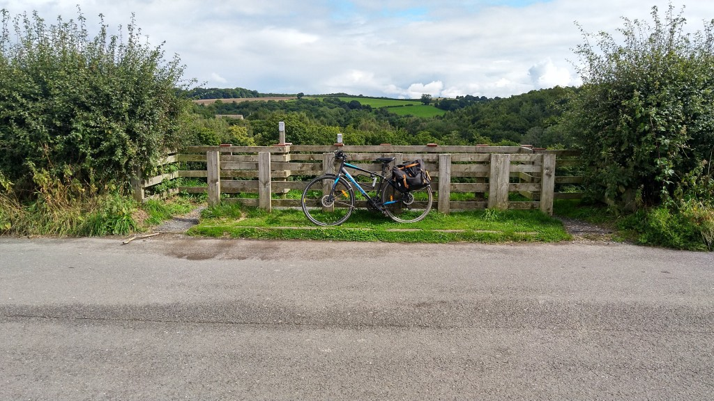 Bike leaning on fence by side of road with fields and hills in the distance