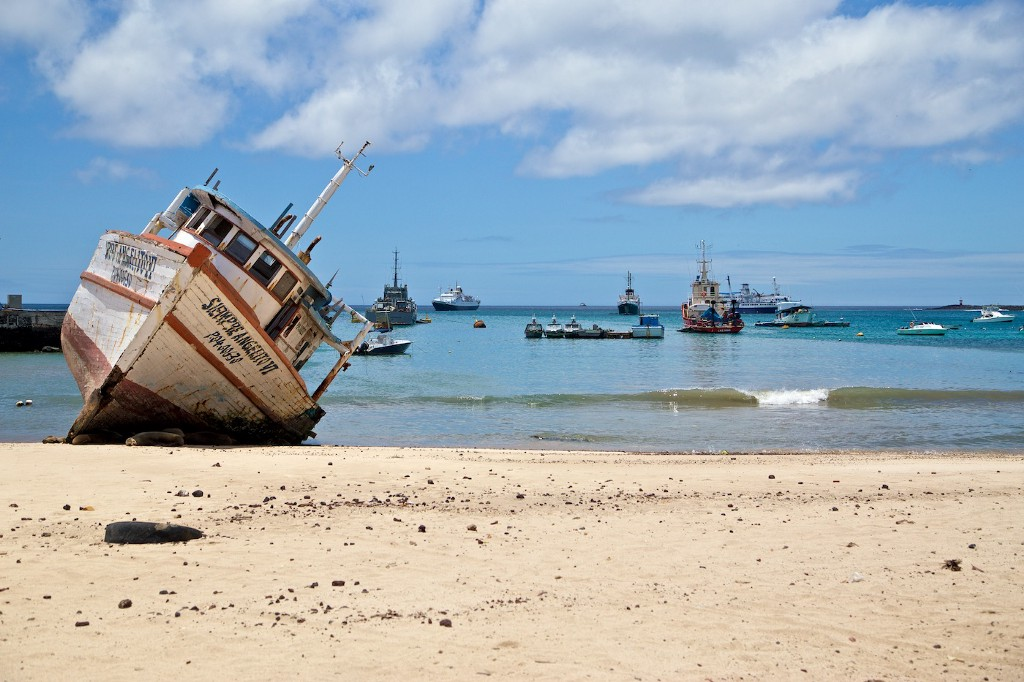 Photos Of The Galápagos Image: A ship run aground is tilted to one side on the shores of the Galápagos Islands; other ships are visible in the distance.