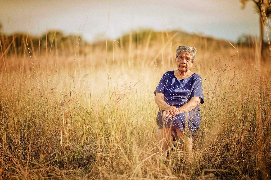 old lady in polka dot dress sitting in dry-weeds field with sour expression