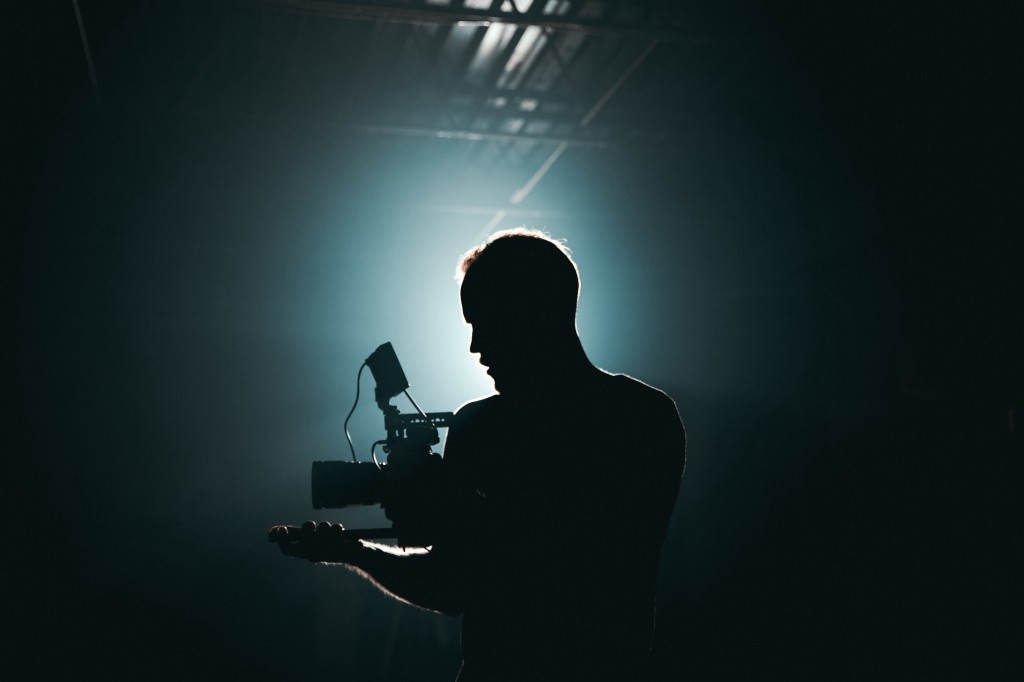 A man holding a video camera in the dark