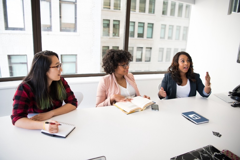 Three Women at a conference table   Photo by Christina Morillo