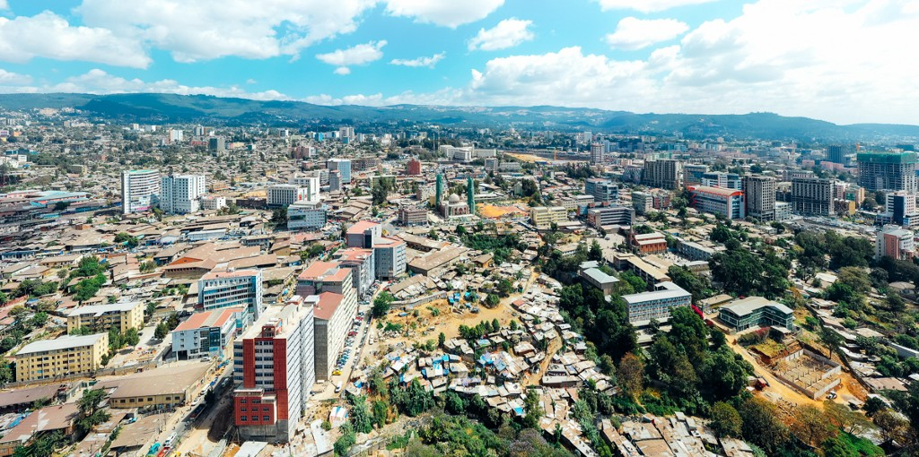 Aerial overview of Addis Ababa with blue skies. The city sprawls into the distance, with rolling mountains far away.