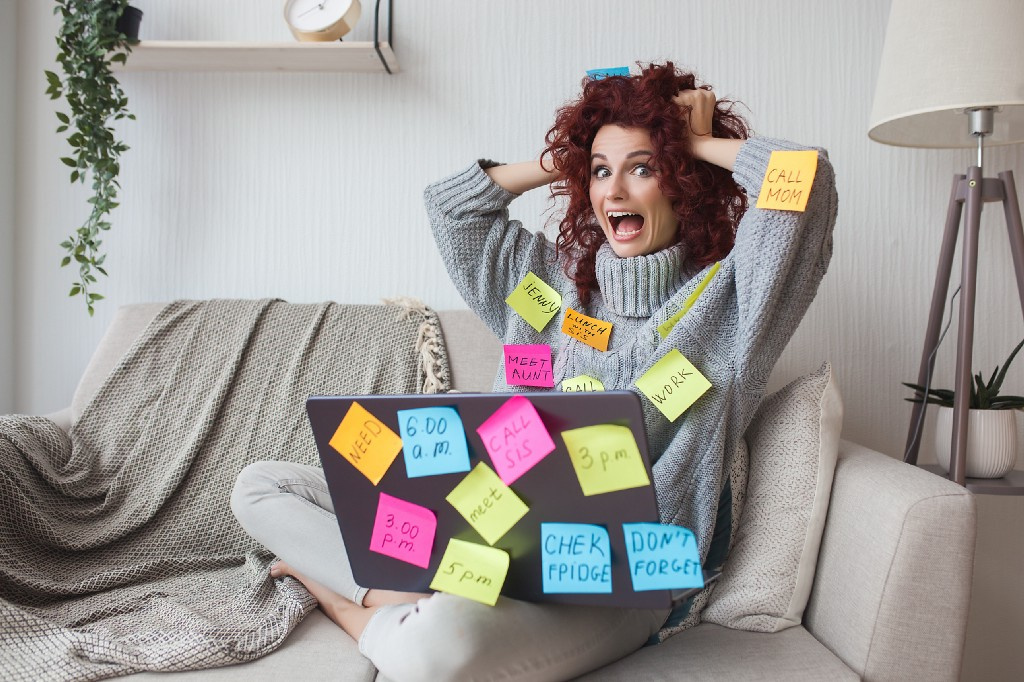 A stressed woman sitting in front of her laptop, clutching her head, covered in post-it notes with various tasks