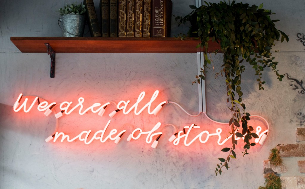 """A red neon sign below a bookshelf that says, """"We are all made of stories."""""""
