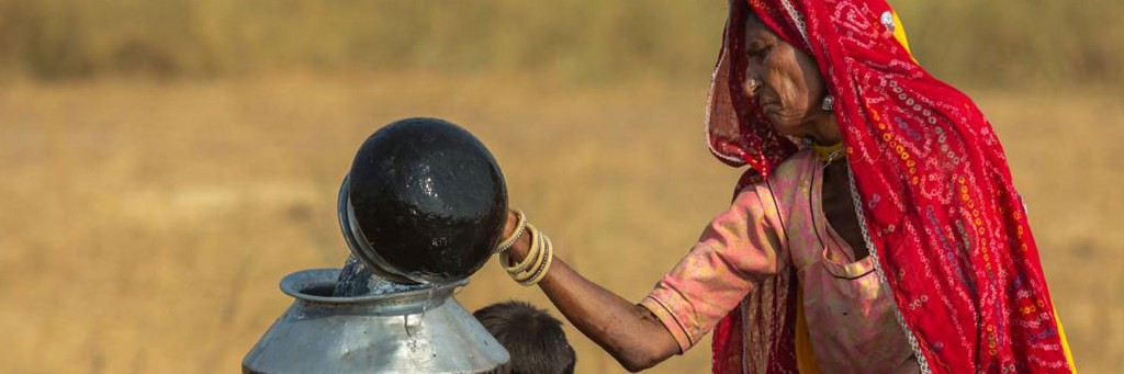 A woman in Pushkar, India, draws water from the well to take to her tent in the desert