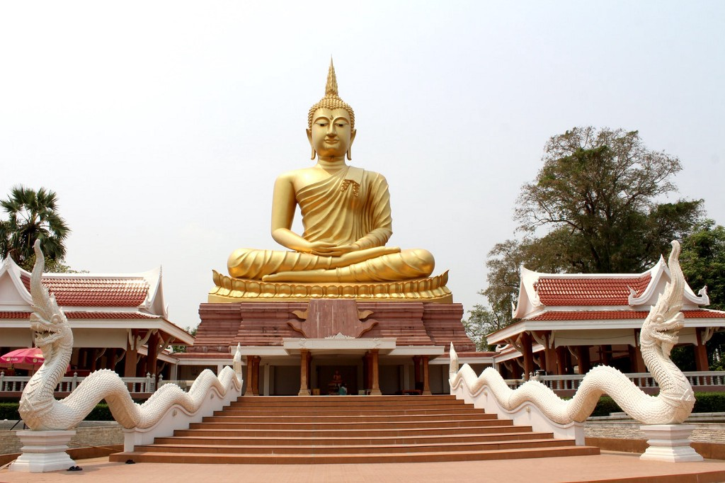 A golden statue of lord Buddha in the middle of a monastary.