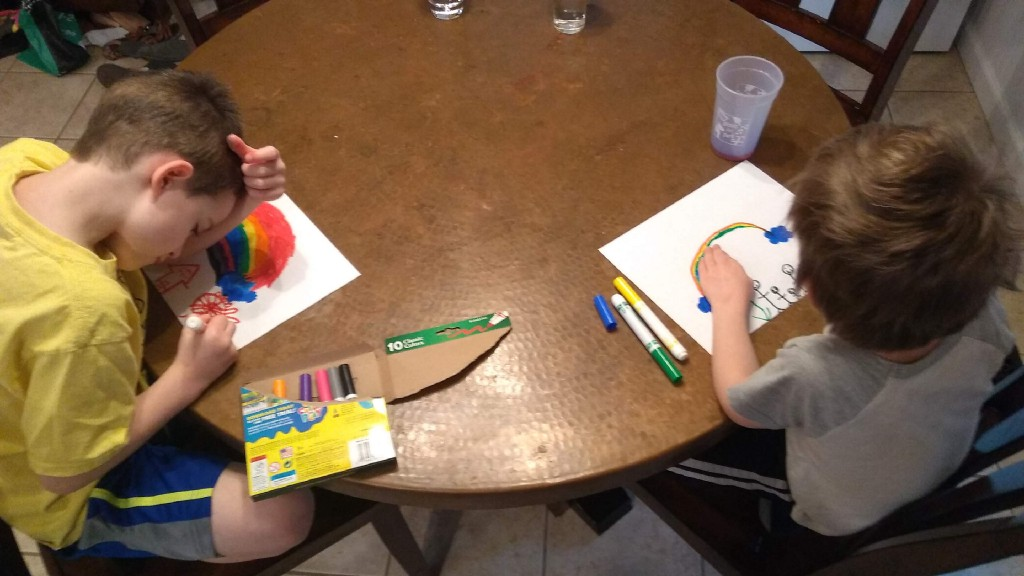 Two kids drawing rainbows at the kitchen table.
