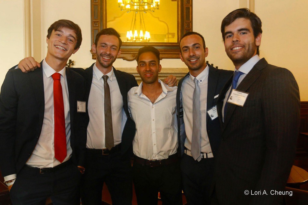5 young men pose with their arms around each other.