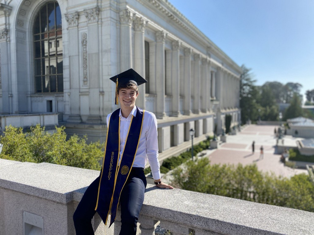 Young man poses with a stole and graduation cap in front of UC Berkeley's Doe Library.