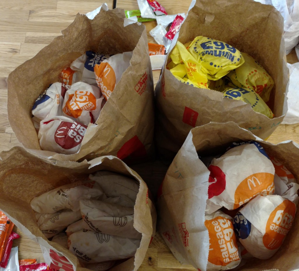 Paper bags piled with wrapped breakfast sandwiches