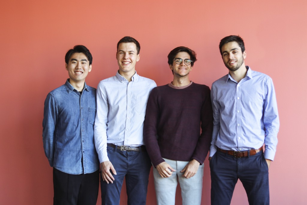 Four business casual dressed young men pose for a group photo in front of a pink wall.