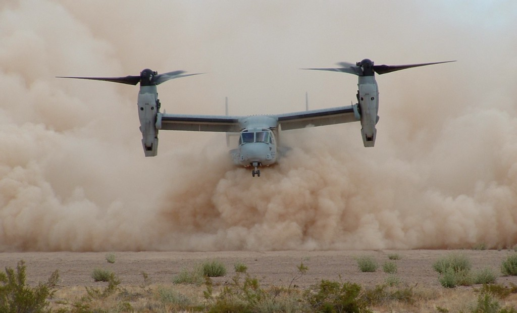 A CV-22 aircraft flying in a dust cloud.