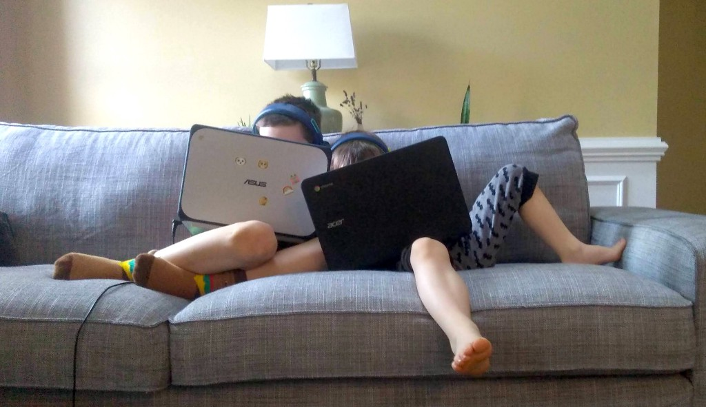 Two kids snuggling on a couch playing on their laptop computers.