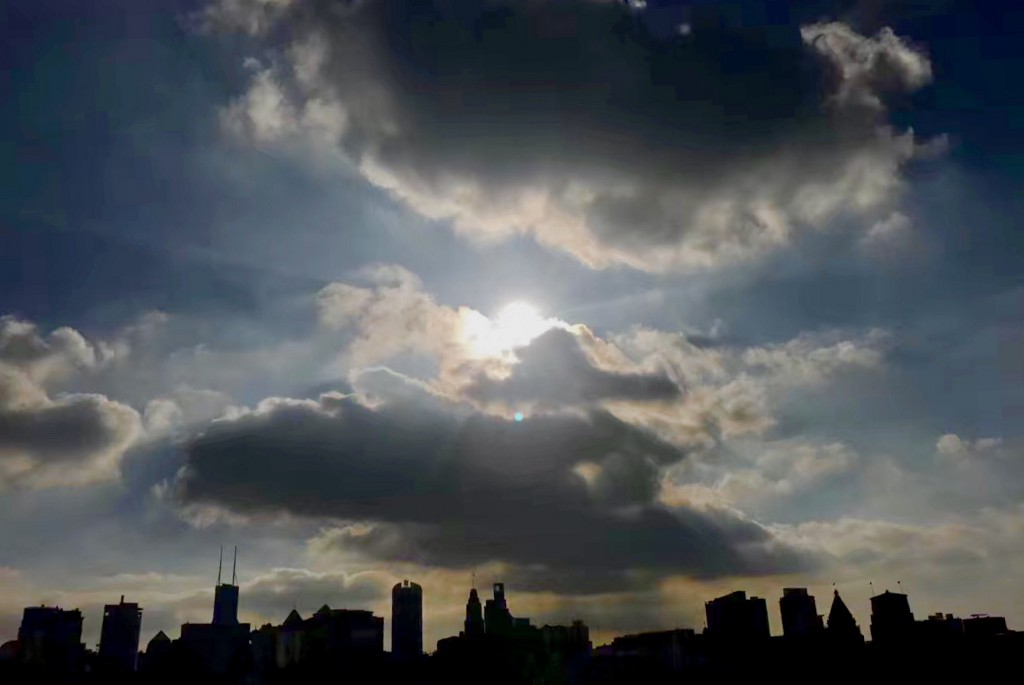 The silhouette of a city landscape, and, in the blue sky, a sun is peering through the clouds.