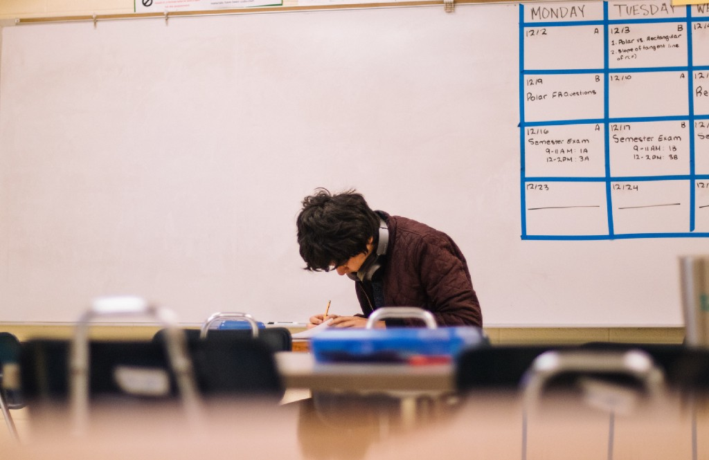 Lonely male student sitting in a classroom writing something