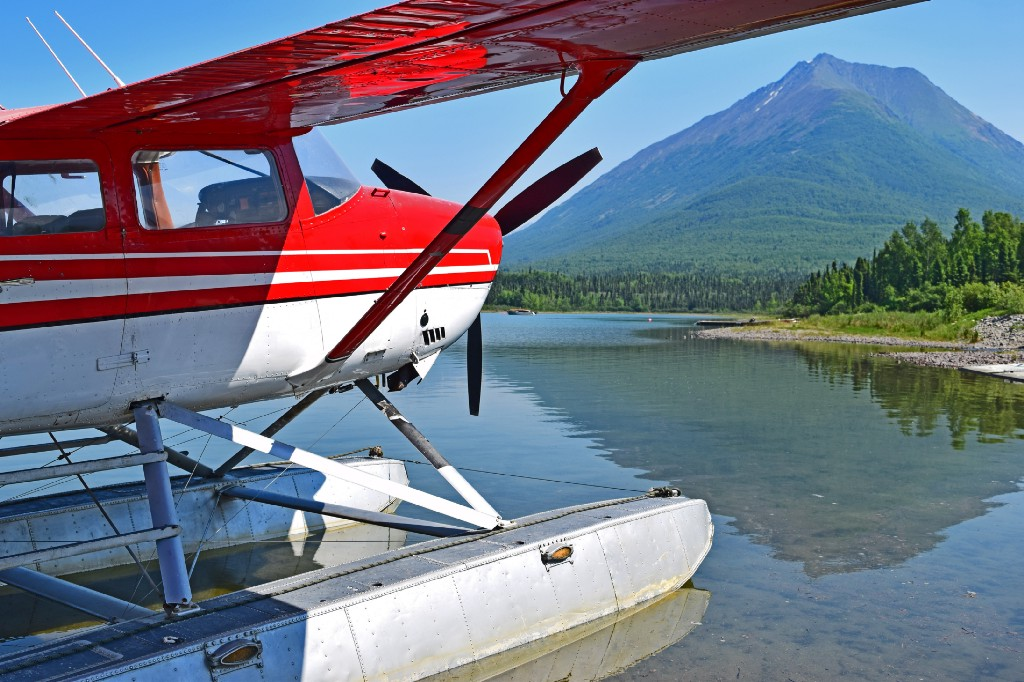A Cessna Stationair docked in a lake in the mountains.