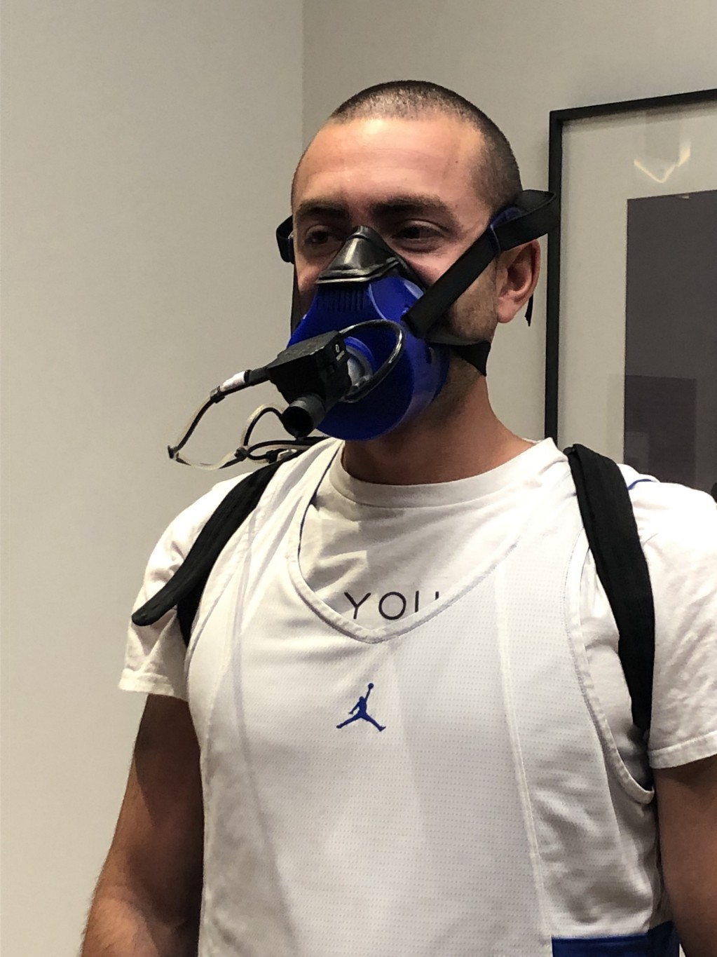 Man wearing a white shirt with a blue mask over the lower half of his face.