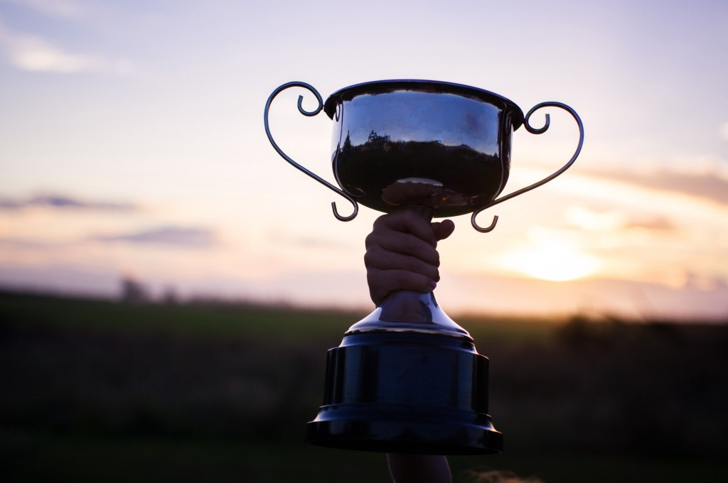 Child holding up a trophy against a sunset.