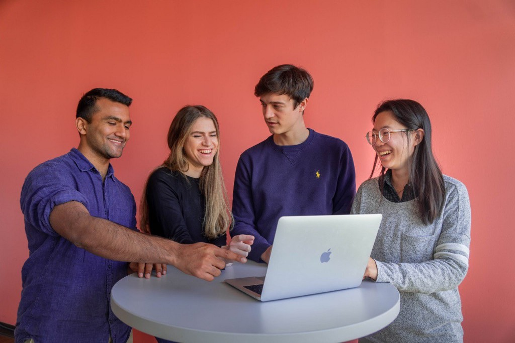 4 young adults smile at a laptop.