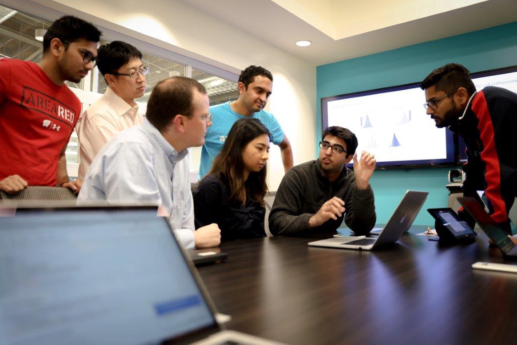 Sundar among a group of students talking in an office space with two laptops, a bright blue wall, and a monitor.